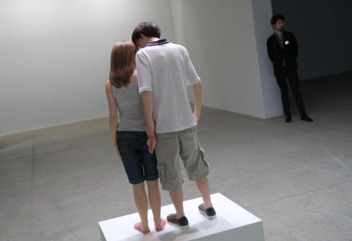 """Vista dorsal de """"Young couple"""". Observe el detalle de las manos, que revela el conflicto: El muchacho tiene a la chica tomada de su muñeca mientras ella extiende su mano hacia atrás."""