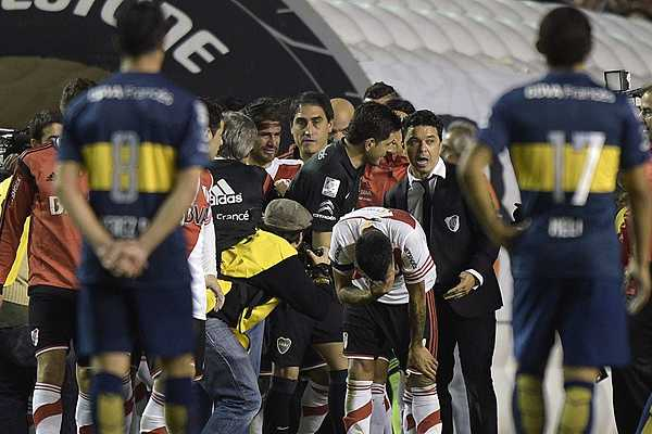Argentina's River Plate footballers react after being pepper sprayed  by Boca Junior supporters before the start of the second half of the Copa Libertadores 2015 second leg football match at the